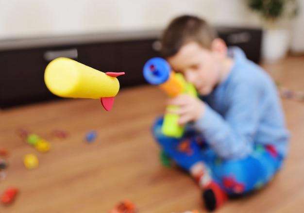 Junge schießt schaumkugeln aus einer spielzeugwaffe