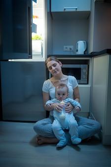 Junge schläfrige mutter sitzt auf der küche mit ihrem kleinen sohn neben dem kühlschrank. konzept der babyfütterung in der nacht