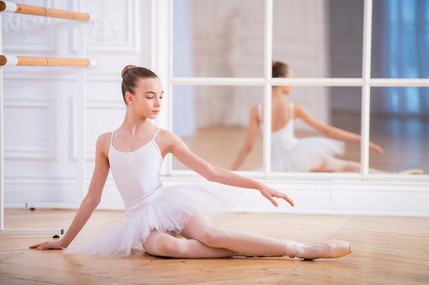 Junge schlanke ballerina in einem weißen tutu, das auf dem boden in einer schönen weißen halle vor einem spiegel sitzt.