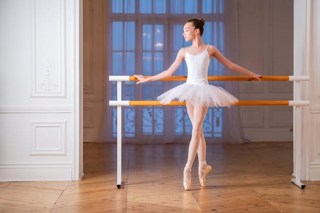 Junge schlanke ballerina in einem weißen tutu, das auf spitze an einer ballettstange in einem schönen weißen saal vor einem spiegel steht.