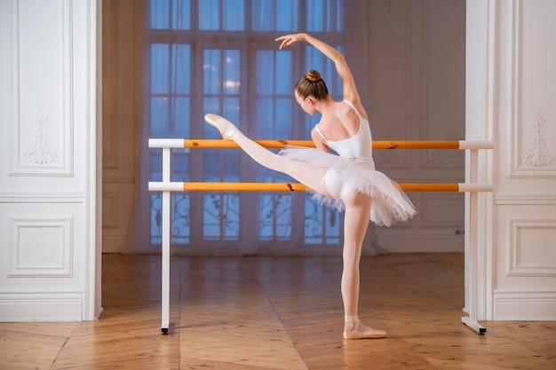 Junge schlanke ballerina in einem weißen tutu, das spitzenschuhe an einer ballettstange in einem schönen weißen saal vor einem spiegel tut.
