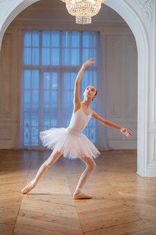 Junge schlanke ballerina in einem weißen tutu tanzt auf spitzenschuhen in einem geräumigen, hellen raum mit großen fenstern.