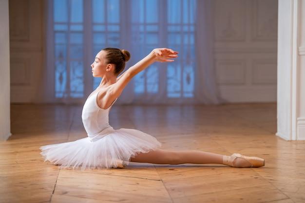 Junge schlanke ballerina in einem weißen tutu tanzt einen schwan auf spitzenschuhen in einem geräumigen hellen raum