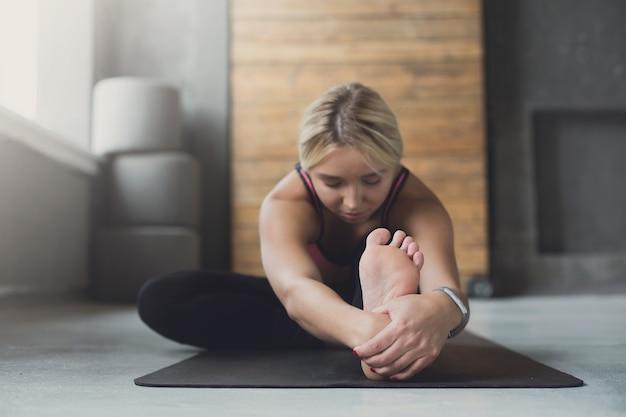 Junge schlanke blonde frau in der yoga-klasse, die asana-übungen macht. mädchen sitzen vorwärts beugen pose. gesunder lebensstil im fitnessclub. dehnen. selektiver fokus auf die beinferse
