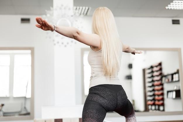 Junge schlanke blonde frau in sportkleidung hält das gleichgewicht bei einem training im fitnessstudio. yoga und gesunder lebensstil. blick von hinten