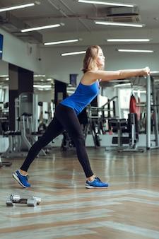 Junge schlanke blonde frau macht übungen im fitnessstudio