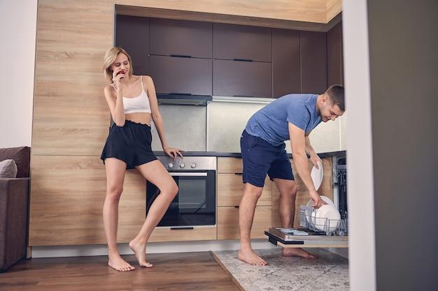 Junge schlanke dame, die roten apfel genießt, während ein mann in blauer kleidung geschirr in die spülmaschine stellt putting