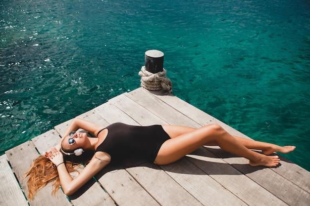 Junge schlanke frau auf pier, mittelmeer, azurblaues wasser, sonnige, gebräunte haut, musik hören, kopfhörer, schwarzer badeanzug, sexy körper, sonnenbaden, tropischer urlaub, entspannt, sonnenbrille
