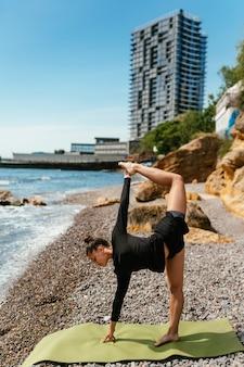 Junge schlanke frau, die übung auf yogamatte im freien am kieselstrand durch das meer tut