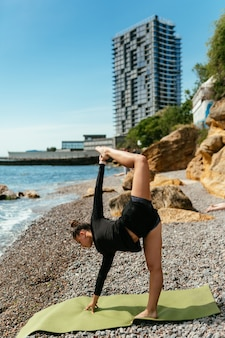 Junge schlanke frau, die übung für muskel auf yogamatte im freien am kieselstrand durch das meer tut