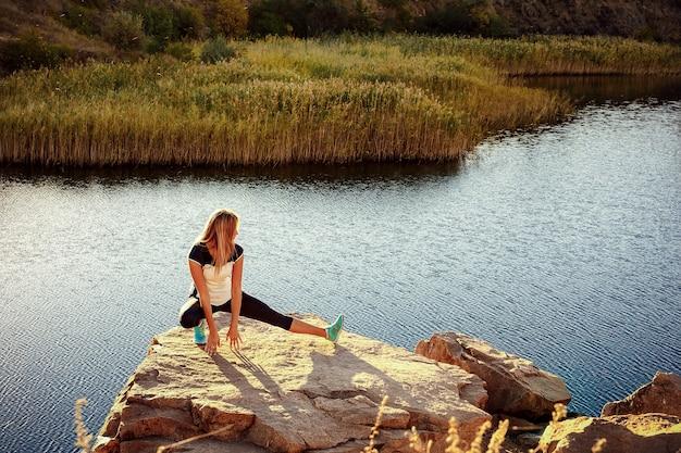 Junge schlanke frau, die yoga draußen auf stein praktiziert