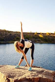 Junge schlanke frau, die yoga im freien praktiziert