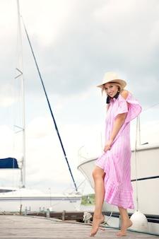 Junge schlanke frau im strohhut und im rosa kleid, die im sommer auf dem pier ruhen