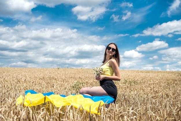 Junge schlanke frau in blau-gelber flagge der ukraine auf weizenfeld im sommer