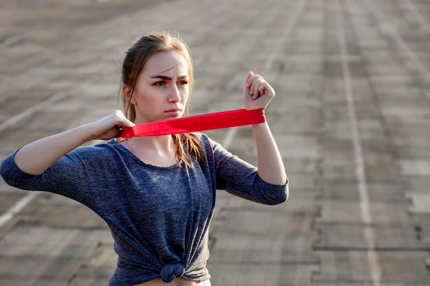 Junge schlanke frau in der sportbekleidung, die kniebeugenübung mit gummiband auf einer schwarz beschichteten stadionbahn tut
