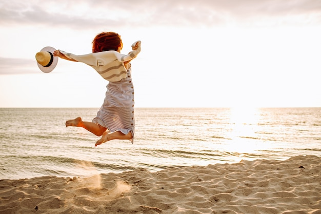 Junge schlanke frau in einem sommerkleid, das am strand bei sonnenuntergang springt. freiheit, abnehmen, sommerferienkonzept.