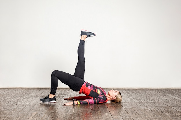 Junge schlanke frau in enger sportkleidung, die yoga praktiziert, eine einbeinige brückenpose mit beinheben macht, flexibilität trainiert, muskelkraft. gesundheitsfürsorge und sportliche aktivität zu hause. indoor-studioaufnahme
