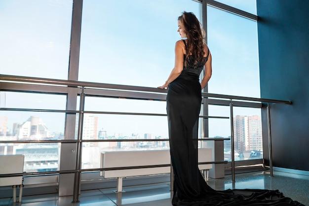 Junge schlanke frau in schwarzem kleid öffnet das panoramafenster im zimmer. traurige traurige frau am großen fenster Premium Fotos