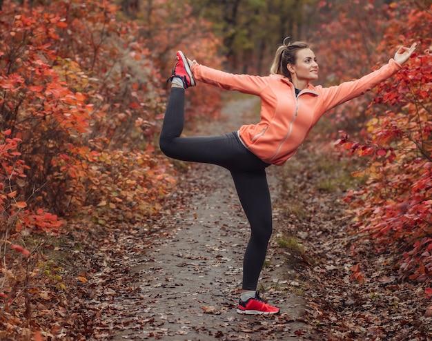 Junge schlanke frau in sportbekleidung, die asana yoga übung im herbstwald praktiziert