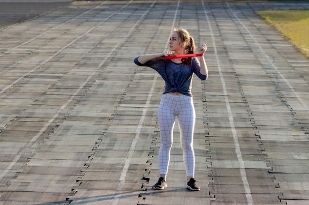 Junge schlanke frau in sportbekleidung, die kniebeugenübung mit gummiband auf einer schwarz beschichteten stadionbahn tut