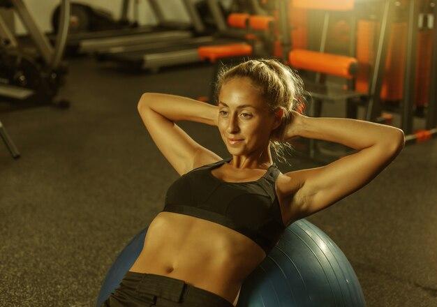 Junge schlanke frau in sportkleidung trainiert bauchmuskeln auf einem fitball im fitnessstudio
