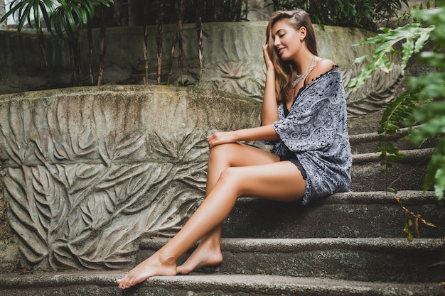 Junge schlanke frau in tropischer bali-villa, die sexy dessous, sinnliche, schöne, flirty, gebräunte haut, trendige kleidung, ethnischen boho-stil, nachthemd, umhang, natürliche schönheit trägt