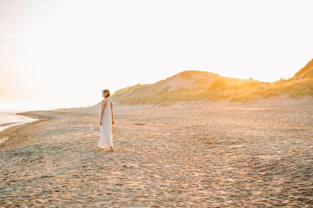 Junge schlanke frau trägt weißes langes kleid und hut allein am strand oder meer oder meer spazieren. exemplar.