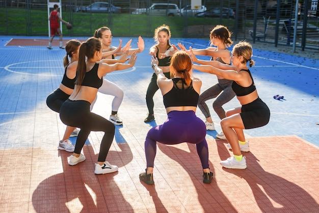 Junge schlanke leichtathletikfrauen, die hockende übungen machen, die im kreis auf dem freiluftstadion im modernen stadtpark stehen.