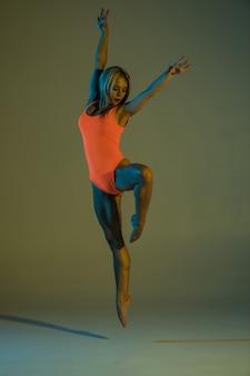 Junge schlanke mädchengymnastik, die akrobatischen stunt tut