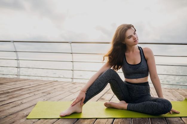 Junge schlanke schöne attraktive frau, die auf yogamatte am morgen auf sonnenaufgang durch meer, gesunden lebensstil, fitnesssport entspannt