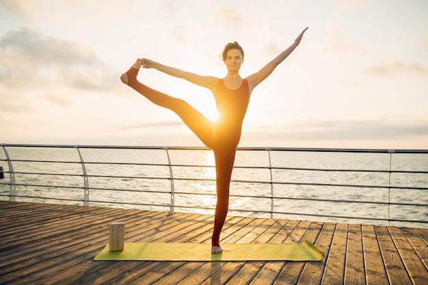 Junge schlanke schöne attraktive frau, die yoga am morgen auf sonnenaufgang durch meer, gesunden lebensstil tut