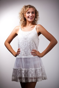 Junge schlanke schöne blonde frau mit lockigem haar im weißen sexy kleid stehend