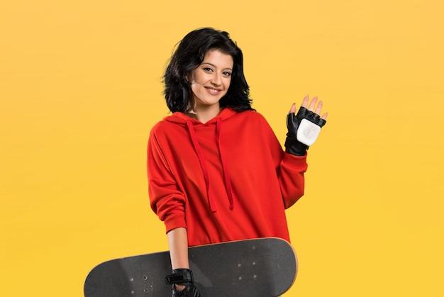 Junge schlittschuhläuferfrau, die mit der hand mit glücklichem ausdruck über lokalisiert begrüßt