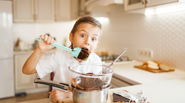 Junge schmeckt geschmolzene schokolade in einer schüssel