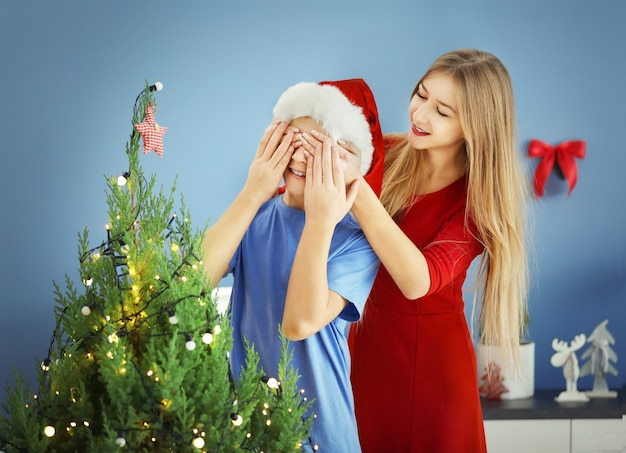 Junge schmückt weihnachtsbaum, während mädchen seine augen schließt, nahaufnahme