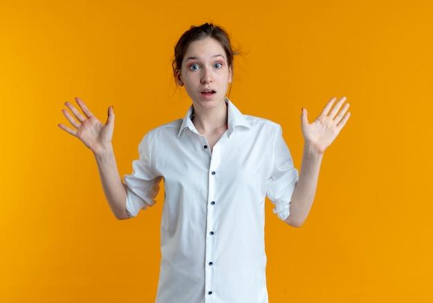 Junge schockierte blonde russische mädchen steht mit erhobenen händen isoliert auf orange raum mit kopie raum