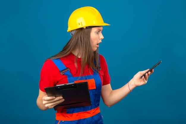 Junge schockierte frau in der bauuniform und im gelben sicherheitshelm, der klemmbrett hält und smartphone in der panik steht auf blauem hintergrund betrachtet