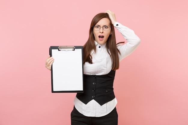 Junge schockierte geschäftsfrau, die sich an den kopf klammert, der zwischenablagetablette mit leerem leerem blattarbeitsplatzkopienraum lokalisiert auf rosa hintergrund hält. chefin. erfolg karriere reichtum. werbefläche.