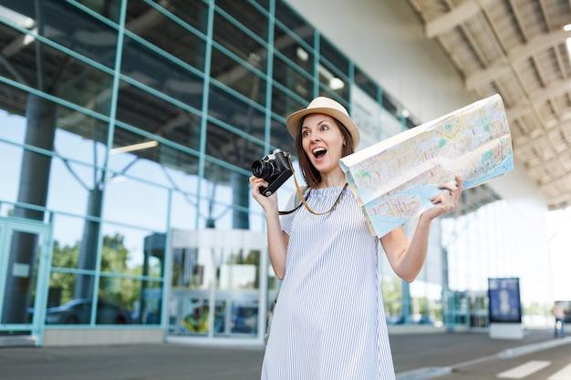 Junge schockierte reisende touristenfrau mit hut mit retro-vintage-fotokamera, papierkarte am internationalen flughafen