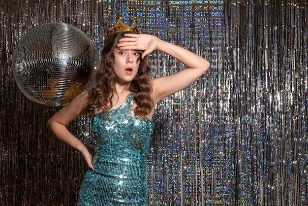 Junge schockierte schöne dame, die blaugrünes glänzendes kleid mit pailletten mit krone in der partei trägt