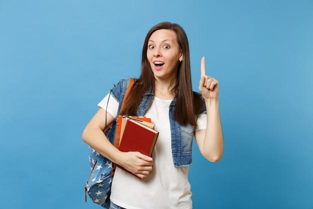 Junge schockierte studentin mit rucksack, die mit dem zeigefinger auf kopienraum zeigt und eine neue idee hat, schulbücher einzeln auf blauem hintergrund zu halten. bildung im hochschulkonzept der high school.