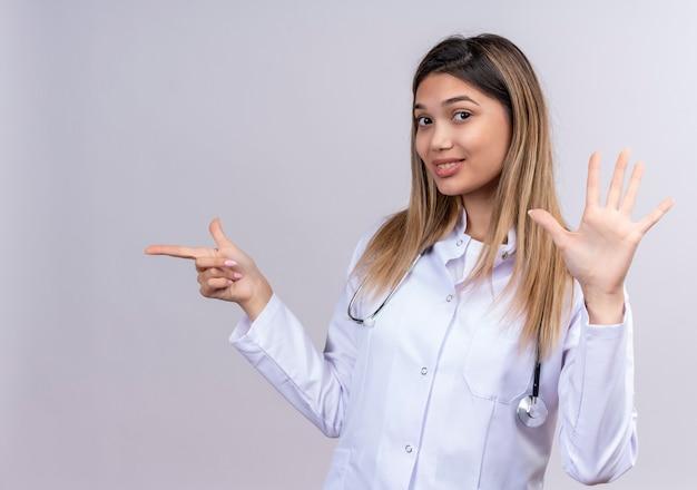 Junge schöne ärztin, die weißen kittel mit stethoskopisch lächelndem selbstbewusstsein trägt, das nummer fünf zeigt und mit zeigefinger zur seite zeigt
