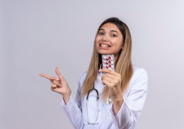 Junge schöne ärztin, die weißen mantel mit stethoskop hält blister mit pillen, die fröhlich mit dem finger zur seite zeigend lächeln