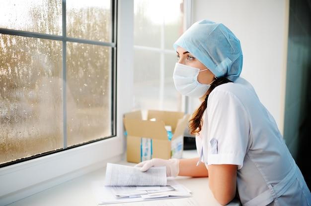 Junge schöne ärztin in einer medizinischen kappe und einer sterilen maske, die durch das fenster schauen