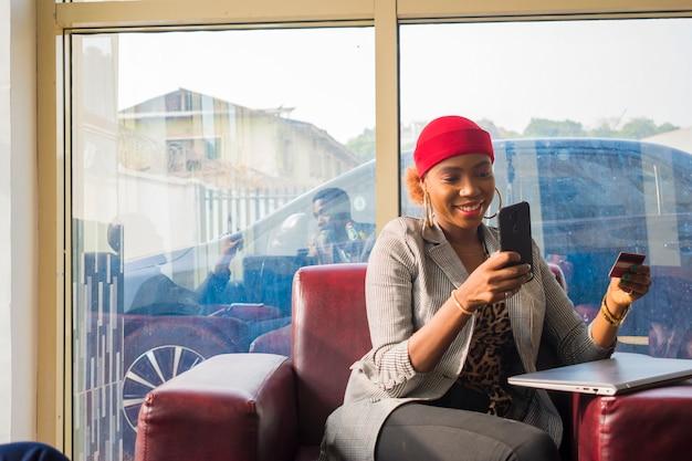 Junge schöne afrikanische geschäftsfrau, die aufgeregt ist, was sie auf ihrem smartphone gesehen hat