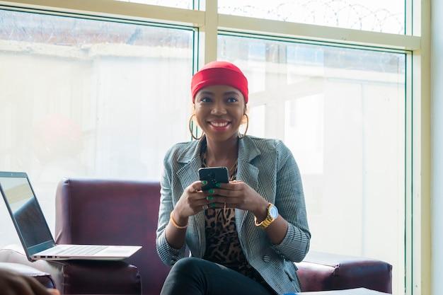 Junge schöne afrikanische geschäftsfrau fühlt sich aufgeregt, während sie ihr handy bedient.