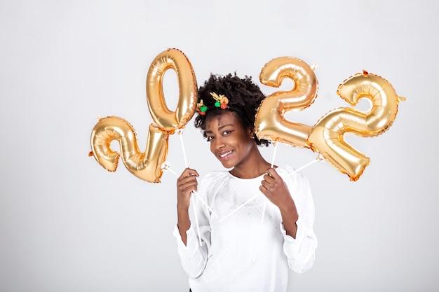 Junge schöne afrikanische rentierhörner auf dem kopf, die ballons 2022 in ihren händen halten. konzept der feier des neuen jahres 2022 goldene zahlenballons