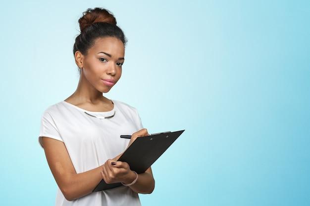 Junge schöne afroamerikanerfrau mit klemmbrett