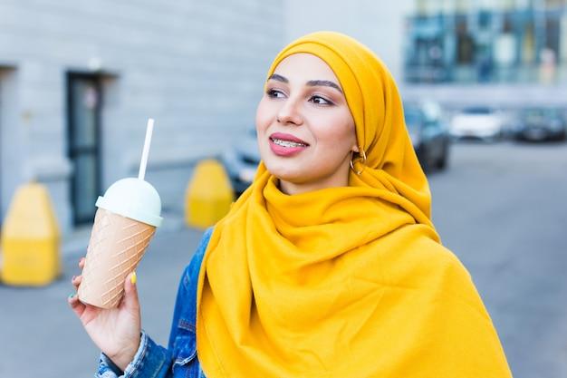 Junge schöne arabische frau im hijab, der kühlenden cocktail im freien trinkt.
