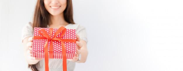 Junge schöne asiatin, die in der hand geschenkbox hält.